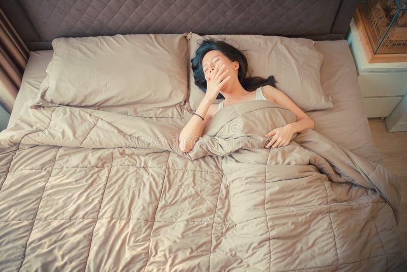 Sömnig asiatisk kvinna som gäspar på säng, bästa sikt arkivfoton