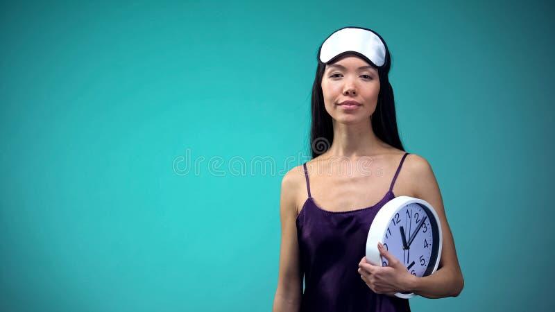 Sömnig kvinna i pyjamasinnehavklockan, betydelse av sömnschema för hälsa royaltyfria foton