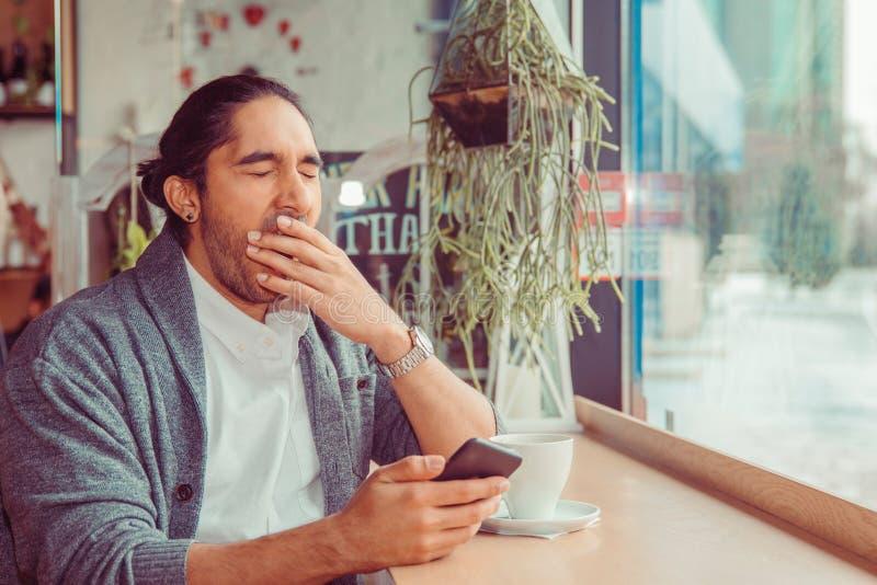 Sömnig rolig man, hand på mun som gäspar se den smarta telefonen som borras av telefonkonversation som smsar royaltyfri foto