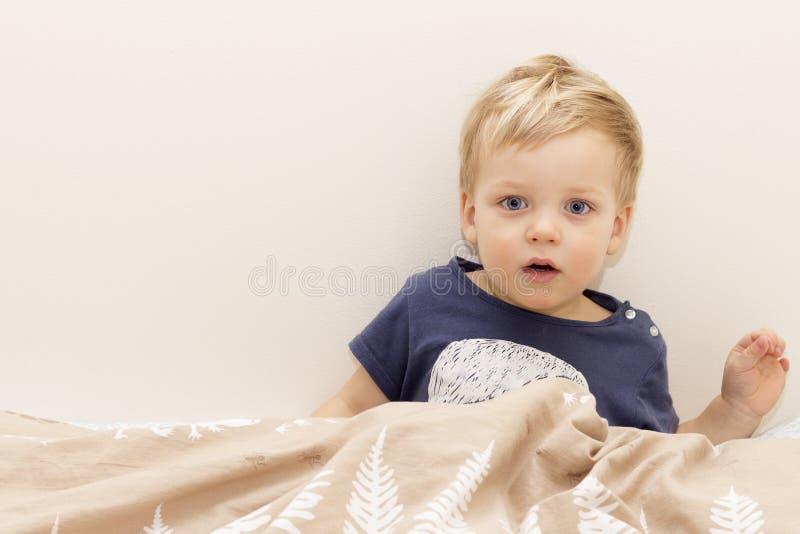 Sömnigt barn i sängen som upp vaknar eller får sömn royaltyfria foton