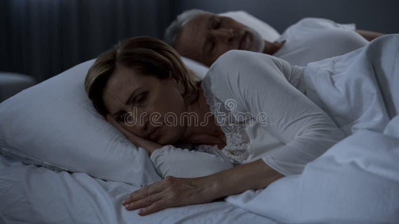 Sömnlös dam som ligger i säng som tillbaka vänds till manlidandeklimakterium, kvinnahälsa arkivbild