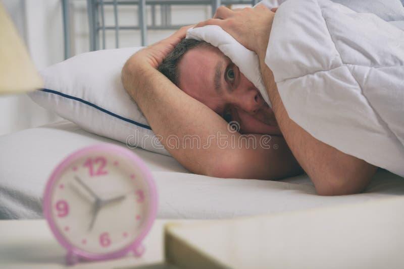 Sömnlös man i hans säng arkivbild