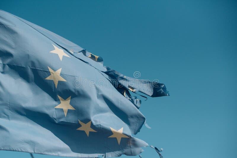 Sönderriven EU sjunker vågen på blå himmel Europeisk facklig flagga med tolv stjärnor på soligt utomhus- Symbol av enhet Euroskep royaltyfri fotografi
