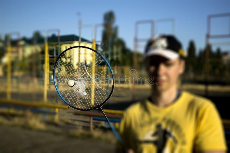 Sönderriven tennisbadmintonracket med fastnad fjäderboll inom under lekmatch arkivfoto