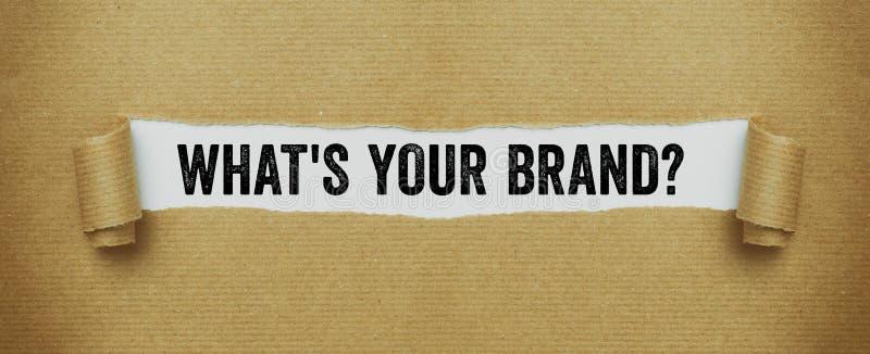 Sönderrivet brunt papper som avslöjer orden vad är ditt märke arkivfoto