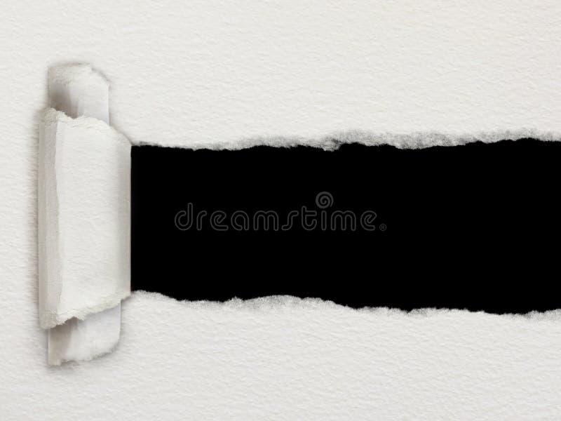 Sönderrivet papper med en svart bakgrund fotografering för bildbyråer