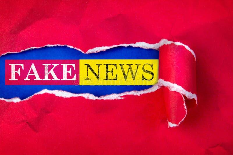 Sönderrivet rött papper och utrymme för FAKE NYHETERNAtext med blå pappers- bakgrund royaltyfri foto