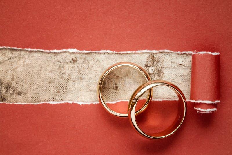 Sönderrivet rött papper och vigselringar fotografering för bildbyråer