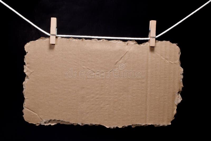 Sönderrivet stycke av papp som hänger på repet som fästas med kläderben arkivfoto