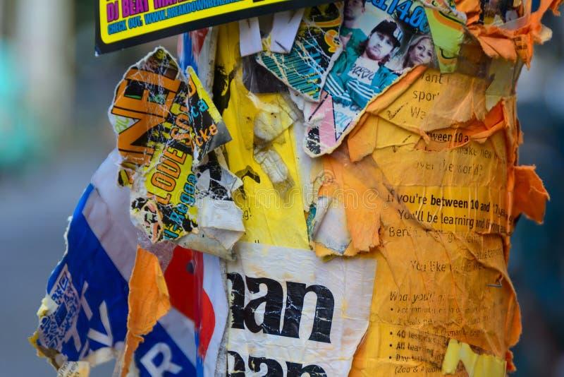 Sönderrivna affischer på lampstolpen i Berlin royaltyfri bild
