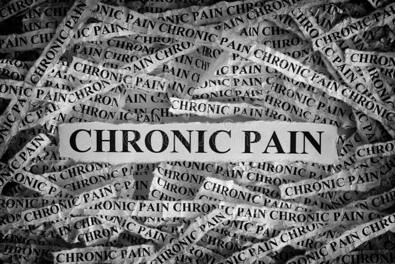 Sönderrivna stycken av papper med de kroniska orden smärtar arkivfoto