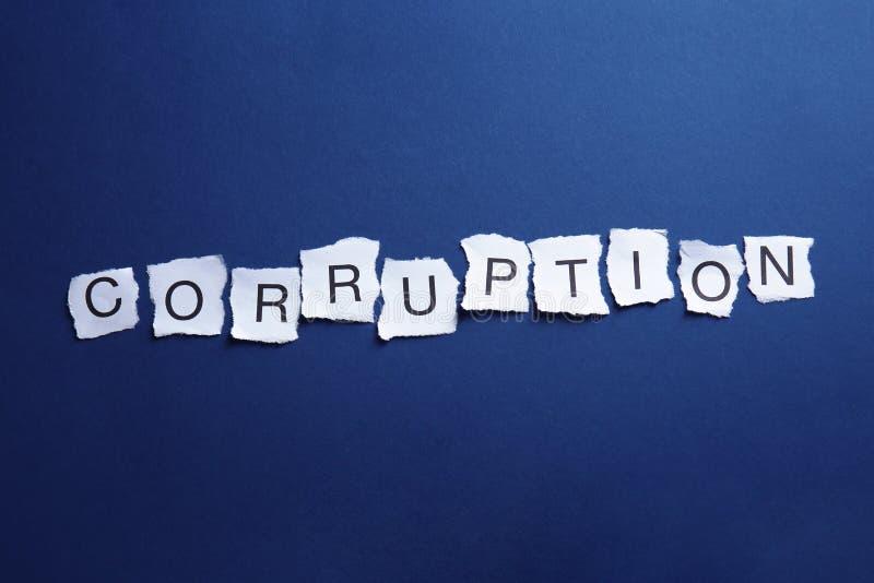 Sönderrivna stycken av papper med ordet KORRUPTION på blå bakgrund royaltyfria foton