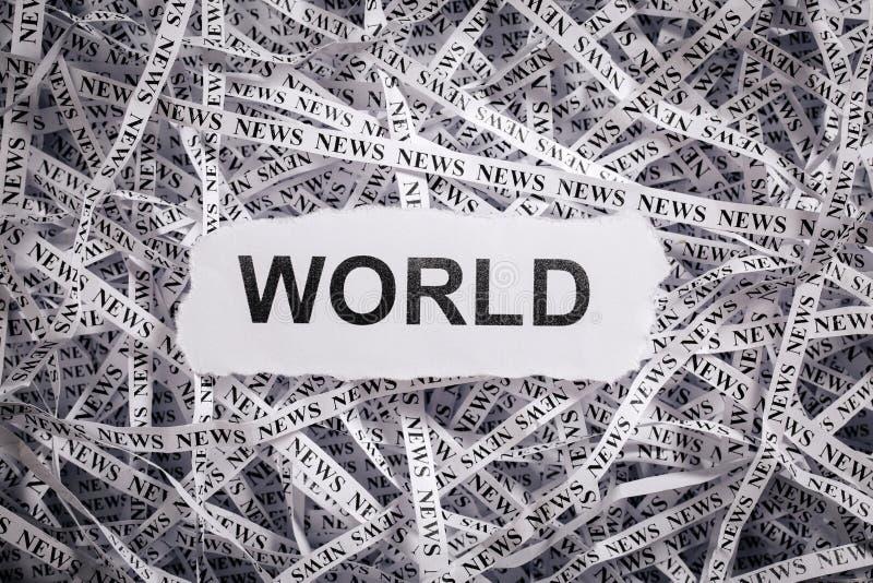 Sönderrivna stycken för Closeup och band av papper med ordet VÄRLD arkivbild