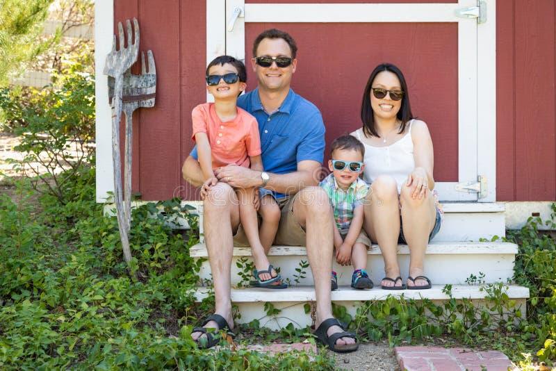 Söner för Caucasian kinesiska par som och för blandat lopp bär solglasögon royaltyfri bild