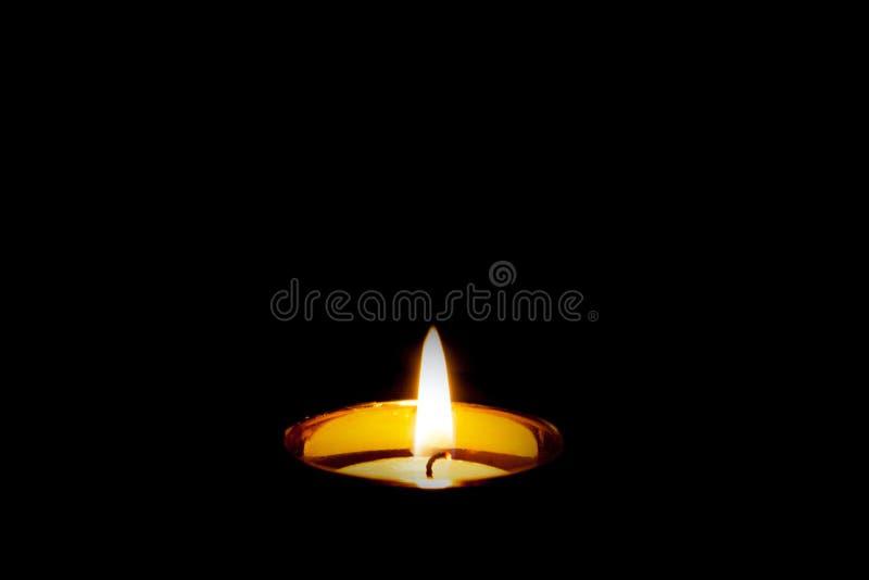 Sörjande begravnings- begrepp Singel isolerad bränningstearinljus på svart royaltyfria bilder