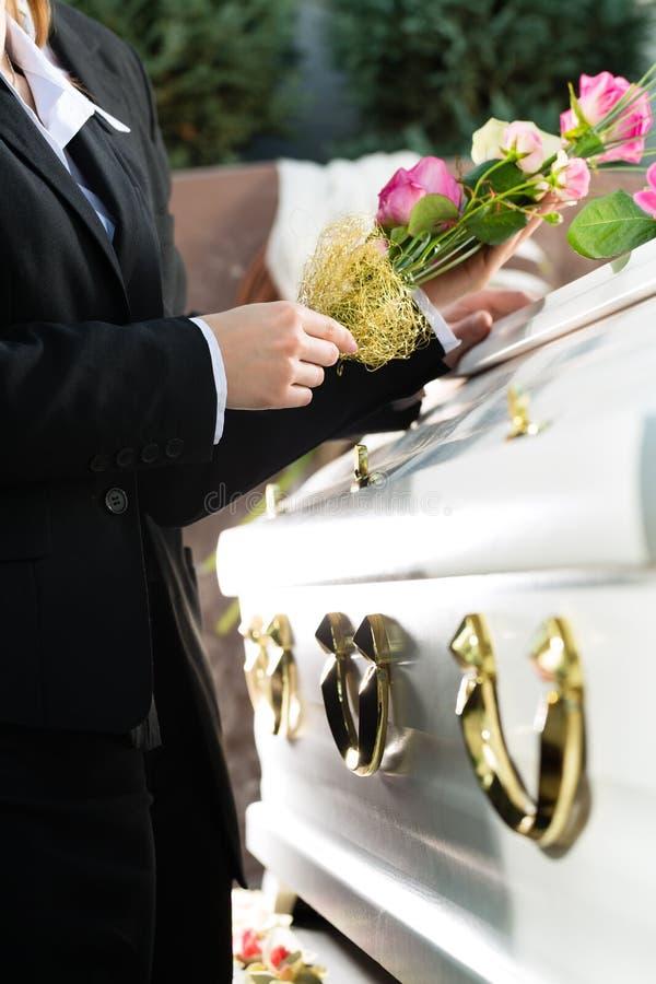Sörjande folk på begravningen med kistan arkivfoton