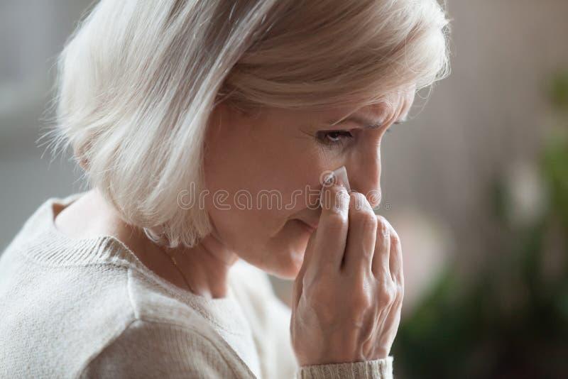 Sörjande gråt för ledsen hög kvinna som torkar revor som sörjer borttappad förälskelse arkivbild