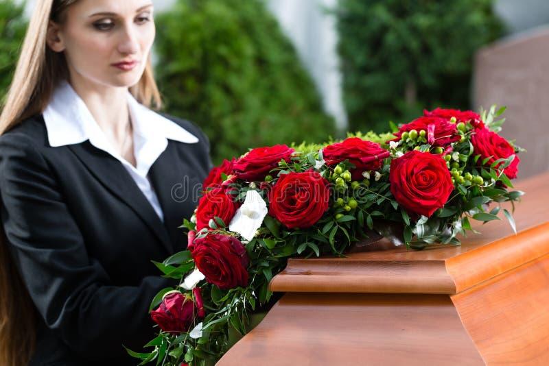 Sörjande kvinna på begravningen med kistan fotografering för bildbyråer