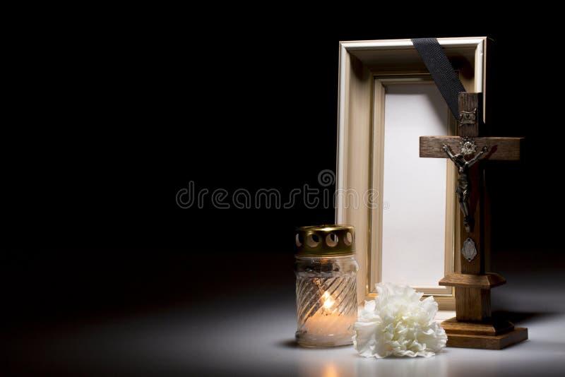 Sörjande ram med korset, blomman och stearinljuset royaltyfri bild