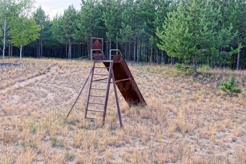 Sörjer brun rostig konstruktion för gammalt järn på en övergiven lekplats i det torra gräset nära träd fotografering för bildbyråer