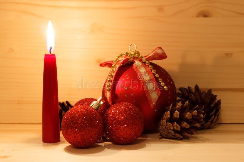 Sörjer röda bollar för nytt år och kottar med en brinnande röd stearinljus på en träbakgrund royaltyfri foto