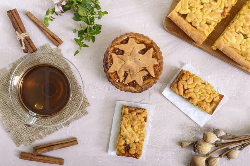 Söt aprikoskaka - tartleten av bakelse fyllde med driftstopp och en kopp te med kanel royaltyfri foto