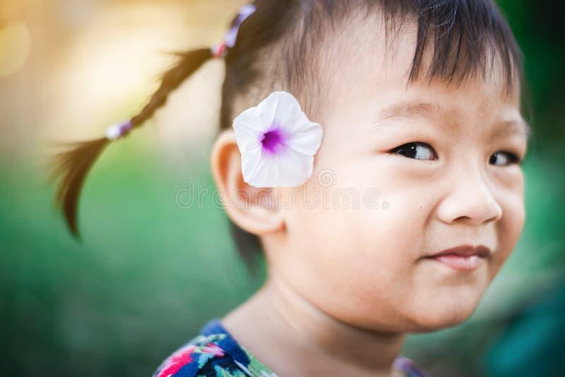 Söt asiatisk barnliten flicka som ler med blomman på hennes öra arkivfoton