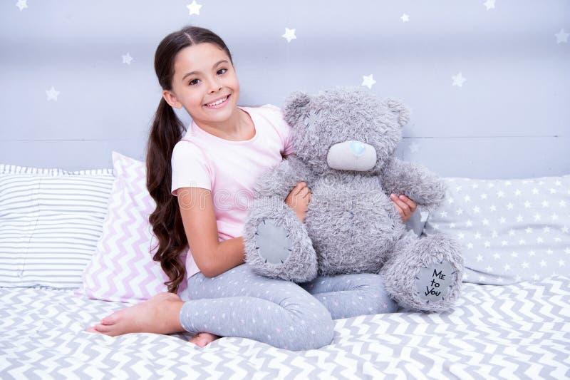 söt barndom Flickabarnet sitter på säng med nallebjörnen i hennes sovrum Ungen förbereder sig att gå att bädda ned Angenäm tid i  arkivfoto