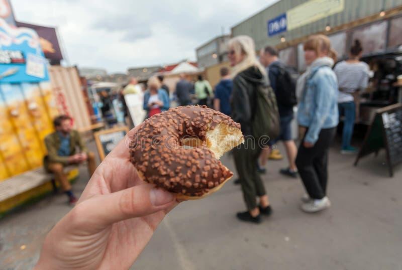 Söt chocolatmunk i hand av besökaren av gatamatmarknaden av Köpenhamnen, Danmark Fritid i Skandinavien fotografering för bildbyråer