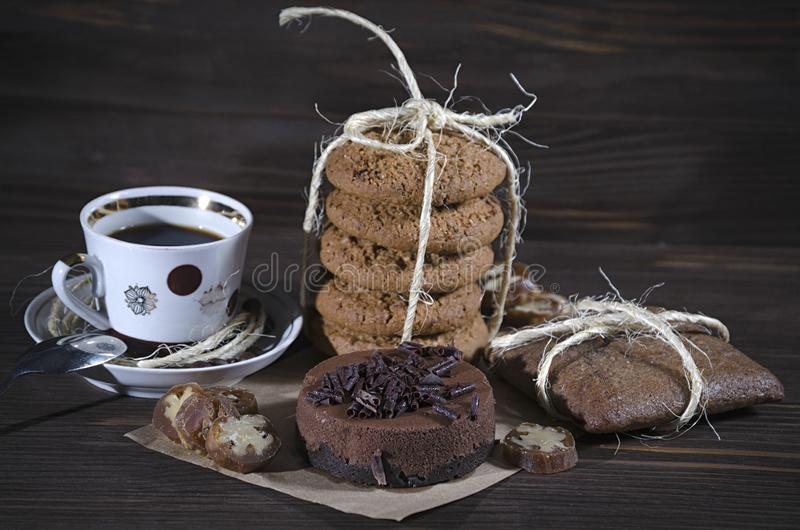 Söt efterrätt med kaffe, chokladostkaka, bunten av havremjölkakor och pepparkakan på mörk träbakgrund, lynne royaltyfri bild