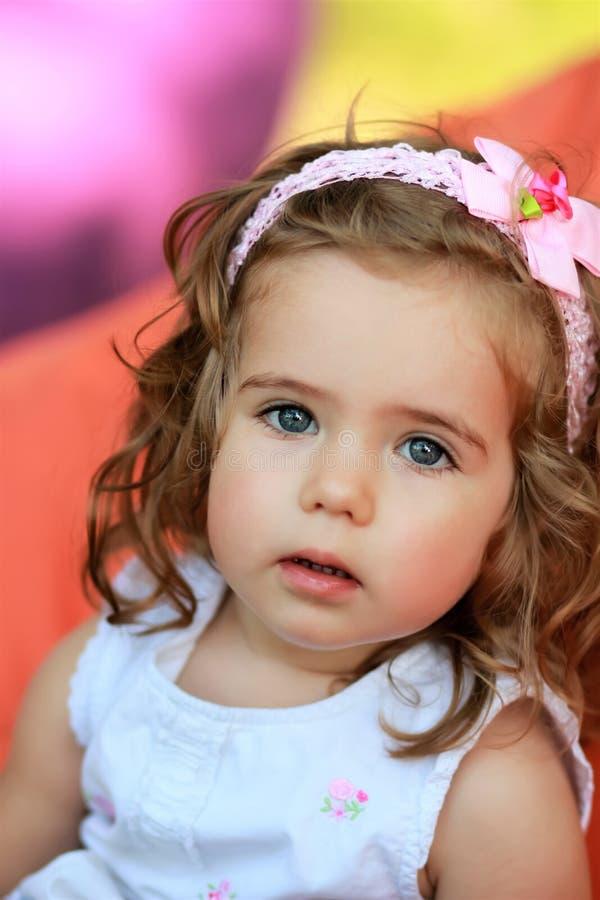 Söt en årig flicka mot suddig ljus färgrik bakgrund royaltyfri foto