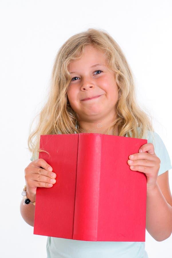 Söt flicka med den röda boken som är främst av vit bakgrund royaltyfria foton