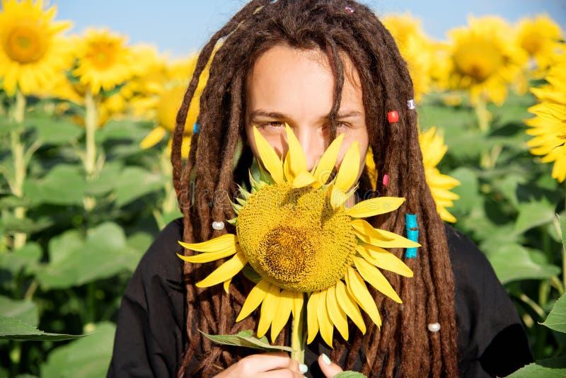 Söt flicka som skelar från solljuset i ett fält med solrosor royaltyfri bild