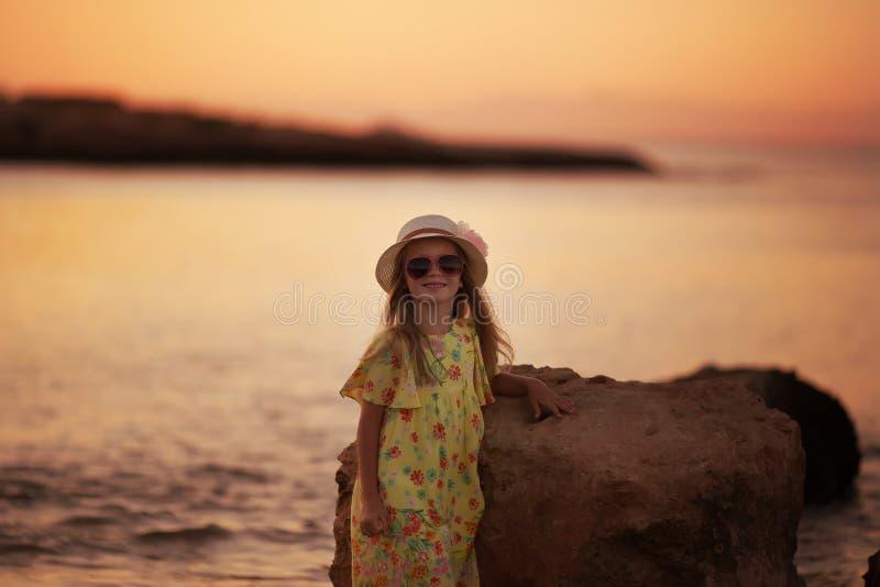 Söt härlig liten flicka av havet på solnedgången royaltyfria foton
