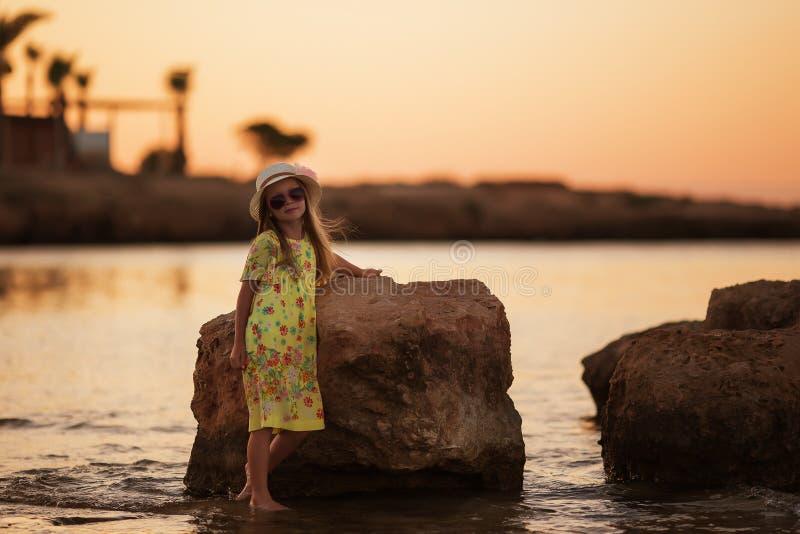 Söt härlig liten flicka av havet på solnedgången arkivfoton