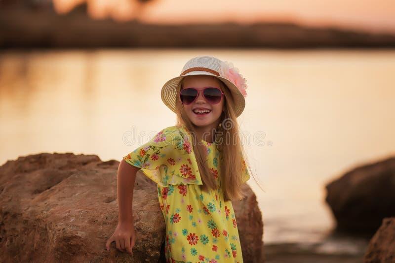 Söt härlig liten flicka av havet på solnedgången royaltyfri fotografi