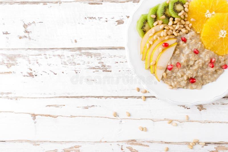 Söt havremjölhavregröt med sörjer muttrar och nya frukter - päron, apelsin, kiwi och granatäpple Sund diet-frukostvegetarian arkivbild