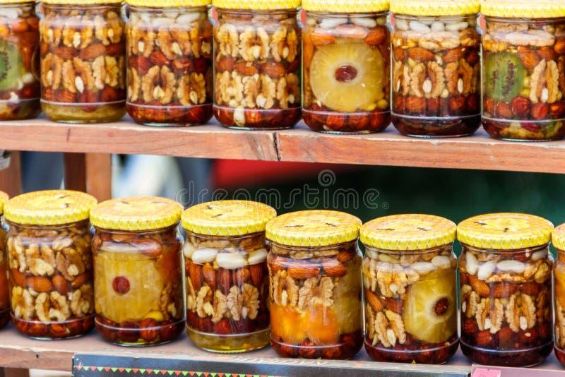 Söt honung med muttrar och frukter i glass krus royaltyfria bilder