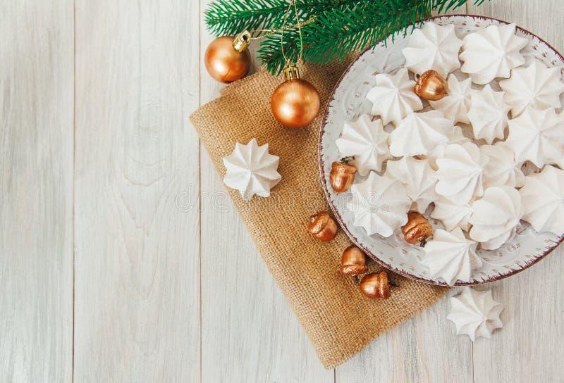 Söt julbakgrund med luftiga marängar, granfilialen, guld- ekollonar och bollar på plattan ungefärlig sackcloth arkivbild