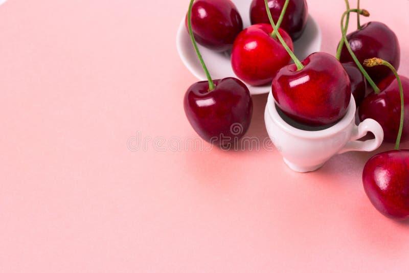 Söt körsbär i den vita koppen fotografering för bildbyråer