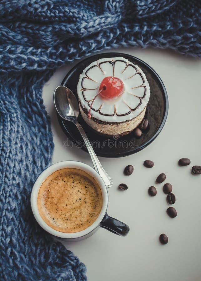 Söt kaka med en körsbär och en kopp kaffe arkivfoton