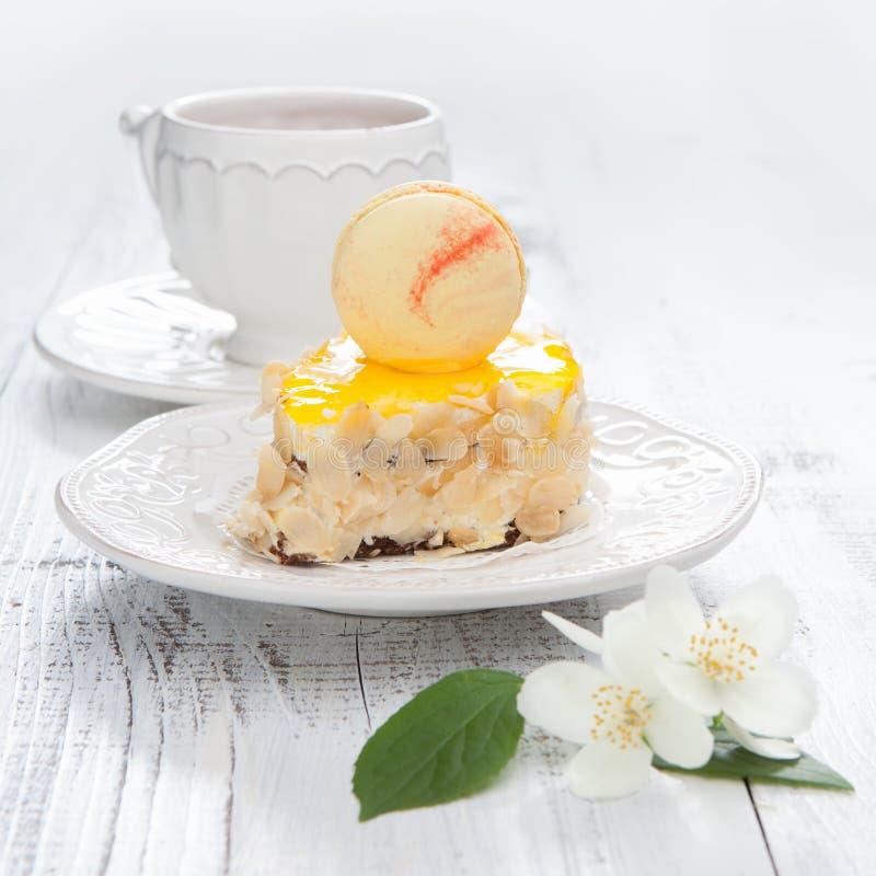 Söt kaka med franska makron på en vit trätabell royaltyfri bild