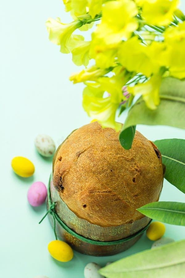 Söt kakaPanettone för hemlagad påsk i för chokladgodis för pappers- form mångfärgade spräckliga ägg spridda på turkostabellblommo arkivfoto