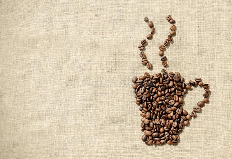 söt kopp för giffel för bakgrundsavbrottskaffe Kaffekorn på bakgrunden av linnetorkduken royaltyfri bild