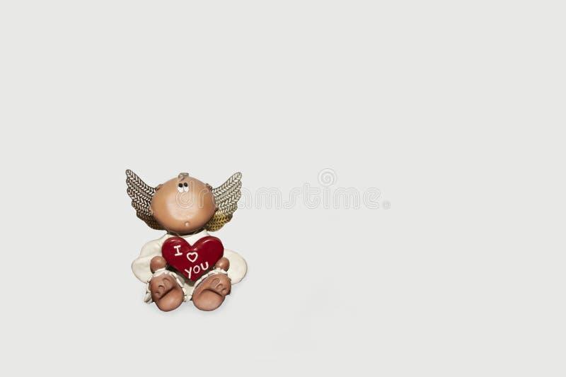 Söt liten ängel som rymmer en röd hjärta royaltyfri bild