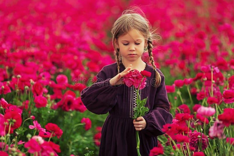 Söt liten flicka i en äng med lösa vårblommor royaltyfri fotografi