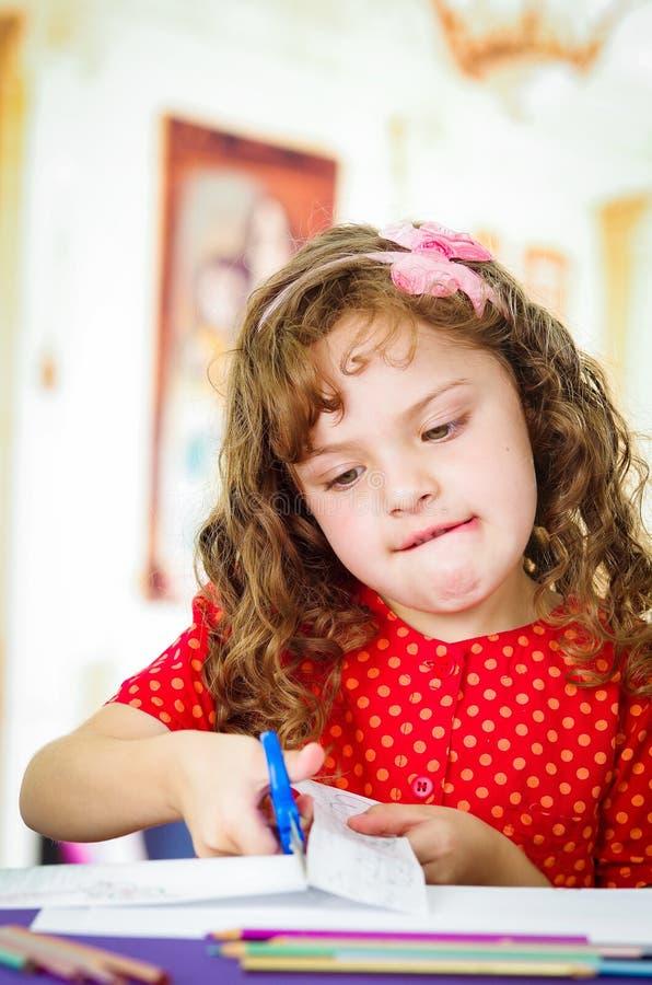 Söt liten flicka som använder sax royaltyfri bild