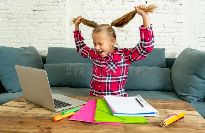 Söt liten grundskolaflicka som drar hennes blonda hår i spänningen som får galen, medan försöka att studera och göra läxa på fotografering för bildbyråer