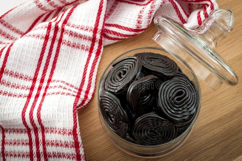 Söt mat och ätligt konfektaffärbegrepp med bästa sikt av en krus med många hjul av den svarta lakritsen i en lantlig inställning royaltyfri fotografi
