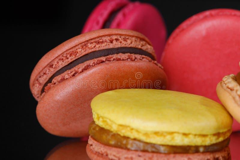 söt och färgrik efterrätt Macarons isolerade på svart bakgrund royaltyfria foton